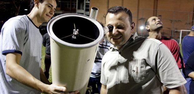 Professor Felipe ajuda alunos da EJA com o telescópio. Imagem: Marina Piedade