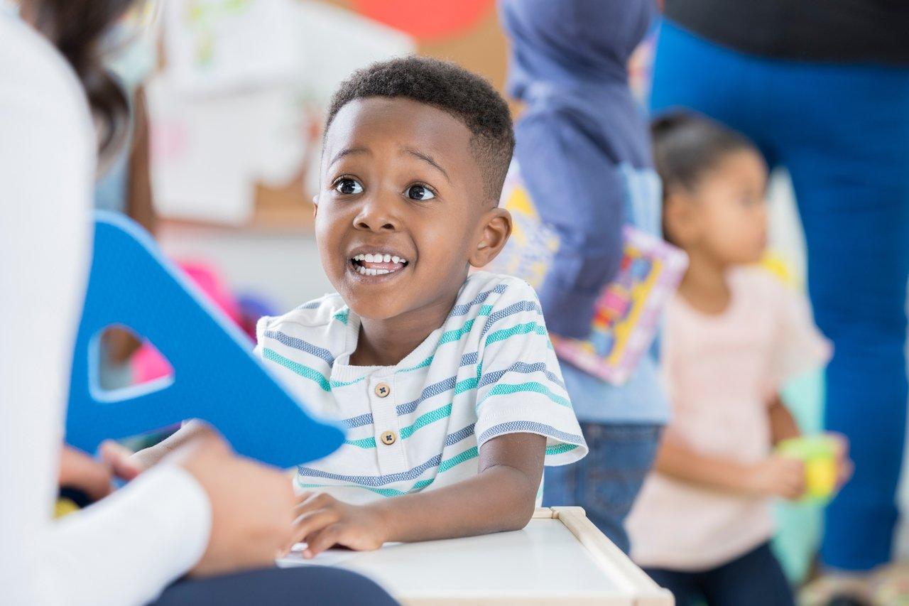 Professora vista apenas de costas entrega uma letra A em azul para criança em sala de aula