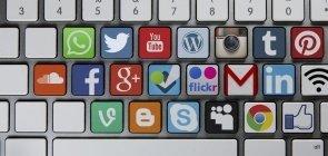 Teclado de um computador Mac de mesa com algumas teclas com as letras substituídas por ícones de redes sociais e ferramentas, como soundcoud, twitter, whatsapp, instagram, wordpress, gmail, skype, blogger, youtube, flickr, facebook, goole plus.