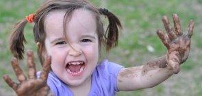 Menina abre um sorriso e exibe as mãos sujas de lama
