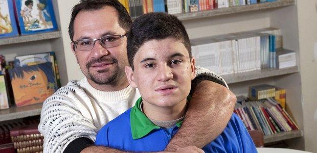 Matheus Santana da Silva, aluno autista, com seu pai na biblioteca da escola. Foto: Marcelo Min