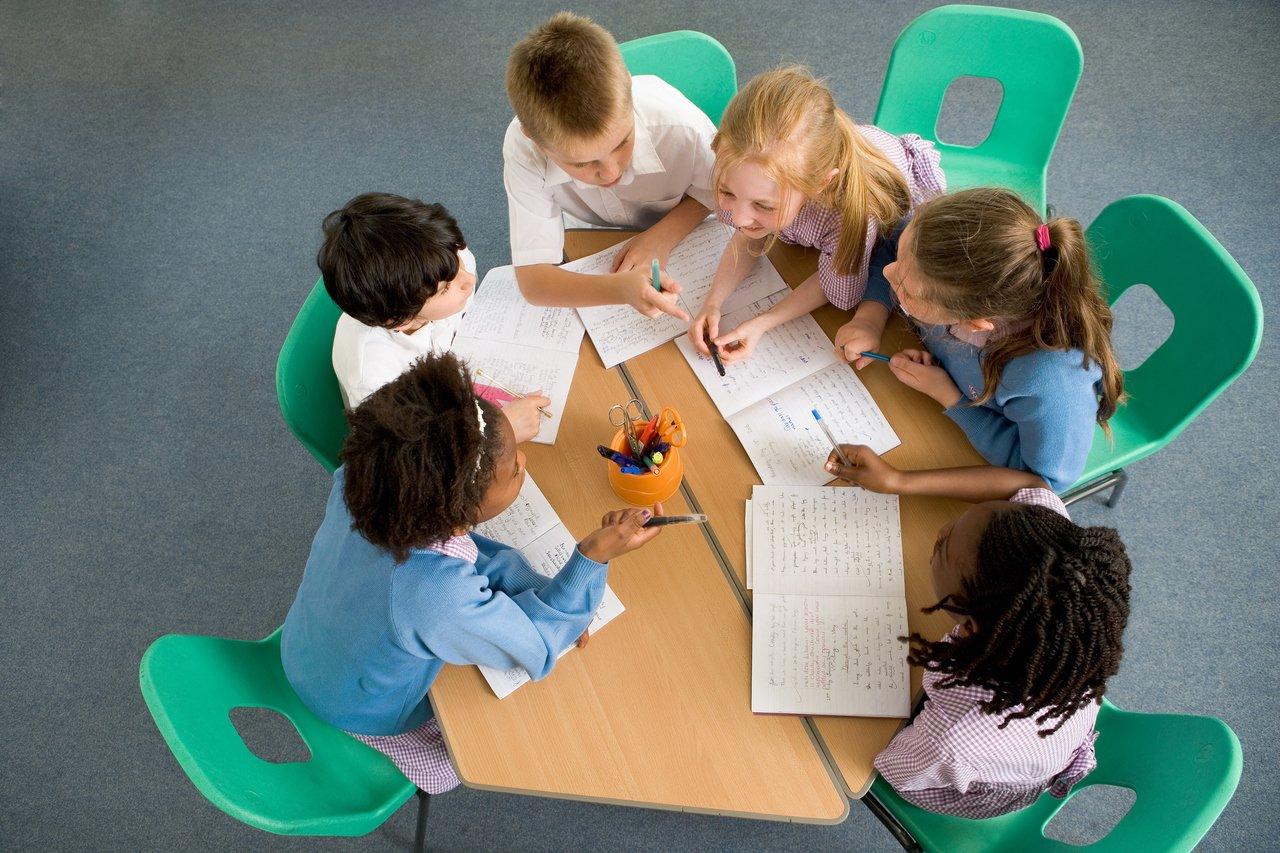 alunos sentados no formato de uma roda com uma mesa verde no centro, eles fazem atividade