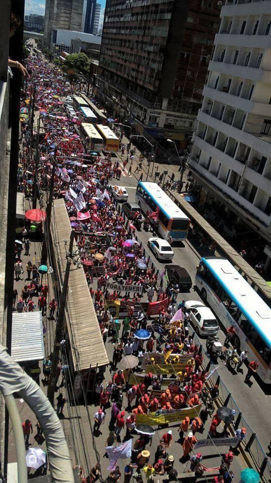 Foto mostra uma rua com pessoas segurando cartazes e protestando ao lado de ônibus