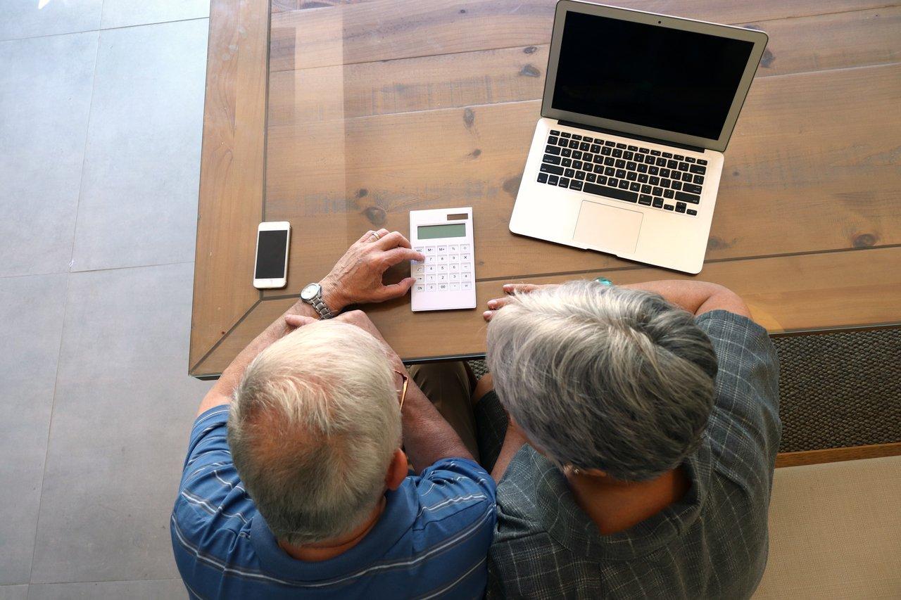 Homem e mulher idosos, de cabelos brancos, sentados em uma mesa em frente a um computador, calculadora e celular, vistos de cima