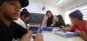 Alunos em grupo escrevem, a professora acompanha eles