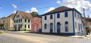 Casas históricas em rua com asfalto de paralelepípedos