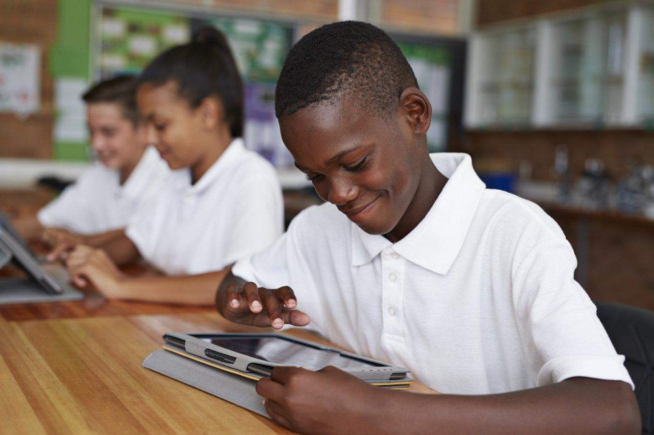 Menino negro sentado em uma mesa escolar com outros estudantes, todos uniformizados com camisas brancas, usa um tablet