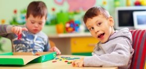 Duas crianças brincam em uma mesa com jogos e brinquedos. Em primeiro plano, uma criança que aparenta ter deficiência intelectual. Em segundo plano, um pouco mais desfocada, uma criança com síndrome de Down concentra-se em seu brinquedo.