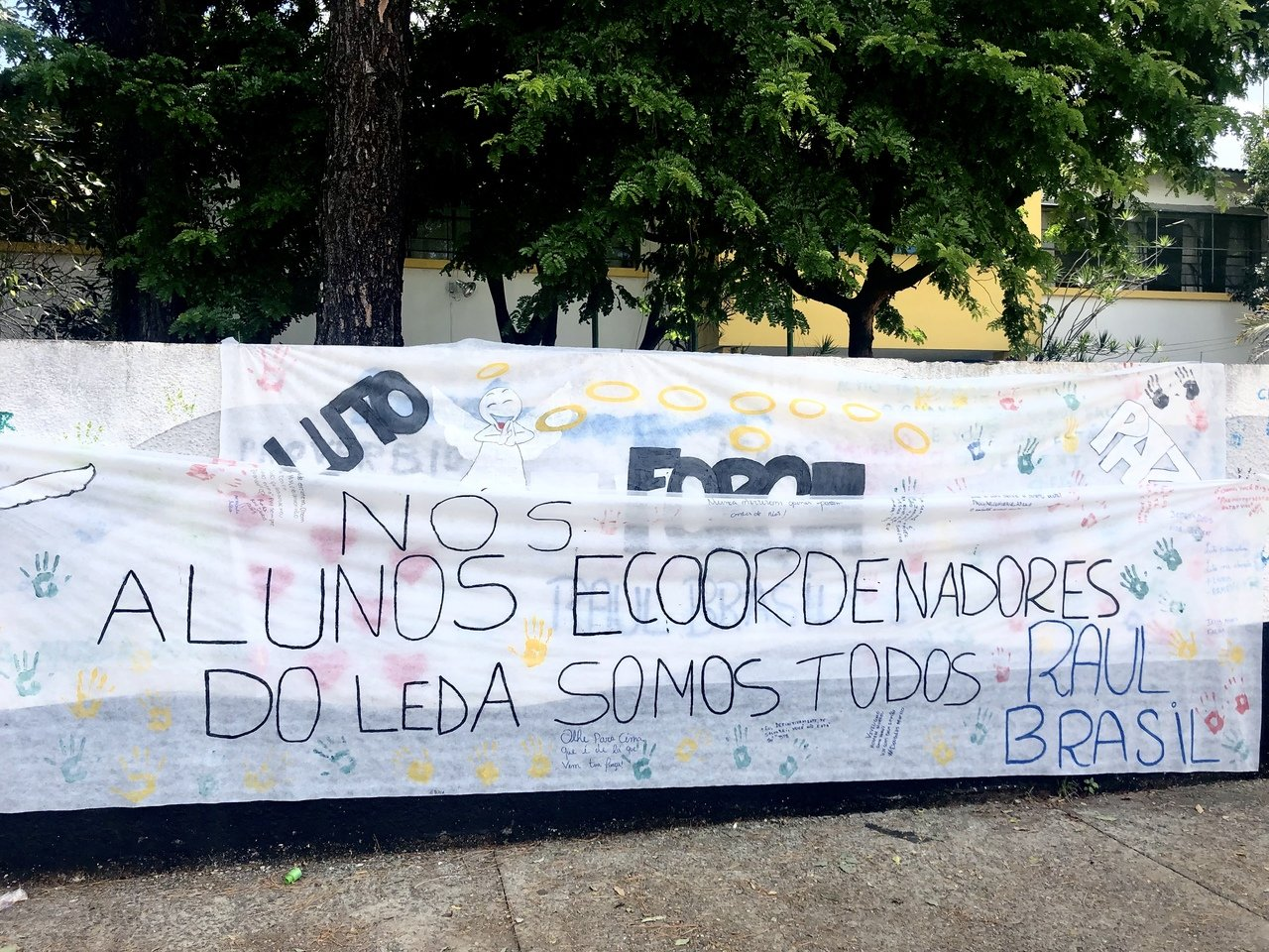 """Faixa pregada em muro com a frase """"nós, alunos e coordenadores do Leda somos todos Raul Brasil"""""""