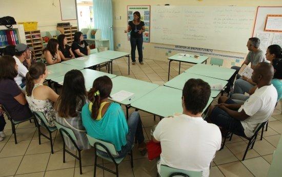 Pais de alunos em uma sala de aula sentados em carteiras organizadas em meio círculo. Uma mulher falando a frente. Crédito: Gabriela Portilho