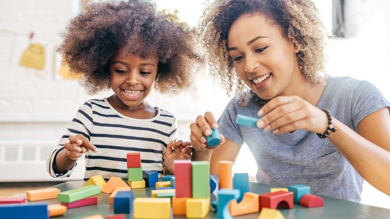 Uma menina de cerca de 4 anos brincando com peças de madeira com a professora. Ambas são negras