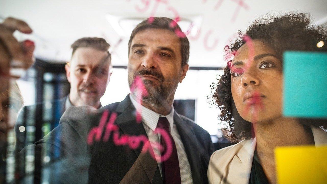 Homens e mulheres reunidos e escrevendo em volta de um quadro transparente