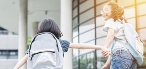 Meninas chegam de mãos dadas à escola