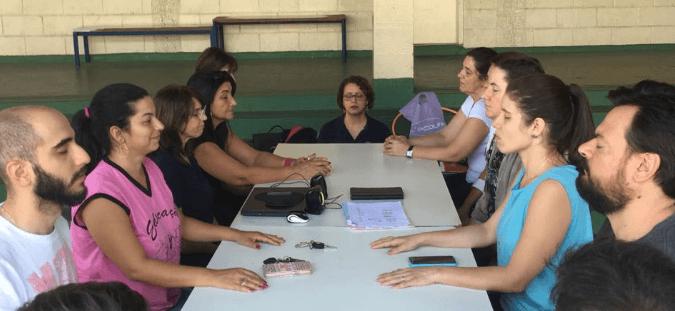 Professores em duas fileiras sentados de olhos fechados fazendo oficina de meditação
