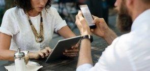 Sem mostrar o rosto, aparecem um homem e uma mulher. Ela de camiseta branca e colar marrom mexe em um tablet e ele de camisa social branca mexe no celular. Na mesa onde estão sentados está um chá gelado e um açucareiro