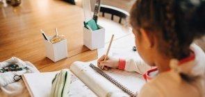 Menina, de costas, escreve em caderno