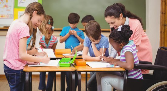 Crianças pintam com um lápis em folha de papel. Professora acompanha menina cadeirante (Foto: Shutterstock)