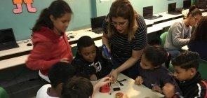 A professora Débora meio curvada em uma mesa com seis alunos construindo um protótipo não identificável