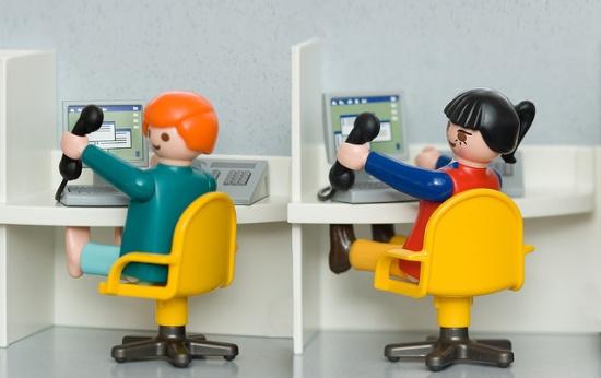 Dois bonecos lego em um cenário de call center