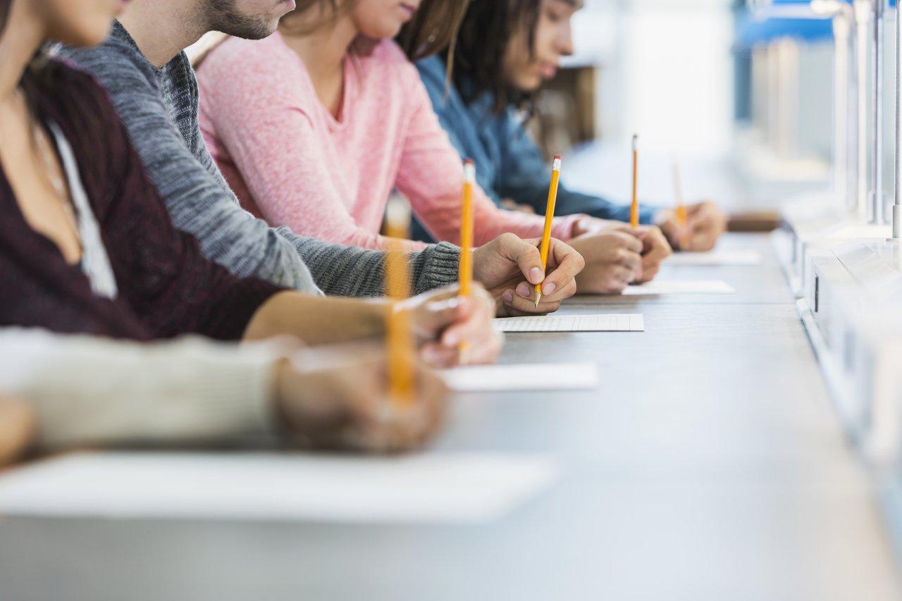 Alunos sentados em mesas enfileiradas escrevendo em um papel com lápis