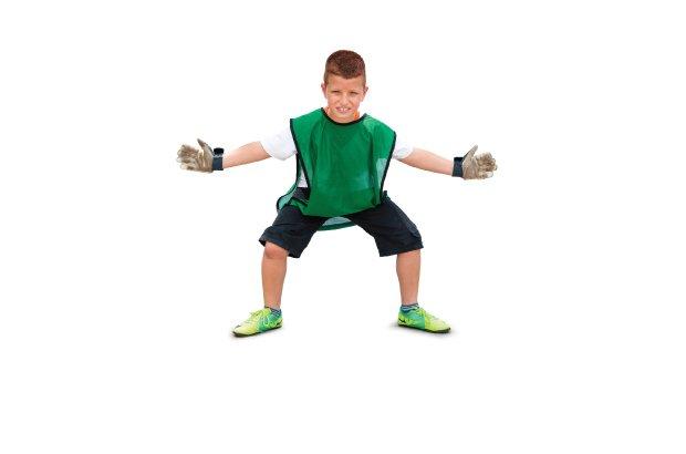 O goleiro se prepara para defender a cobrança da penalidade máxima se posicionando no meio do gol, com os joelhos semiflexionados e os braços abertos