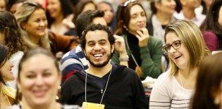 várias pessoas sentadas em uma espécie de auditório sorrindo