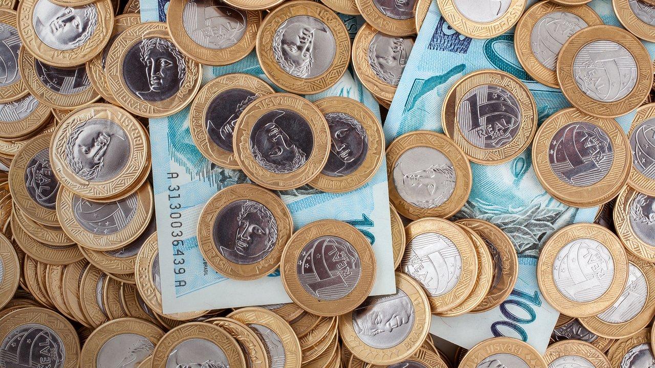 Foto mostra duas notas de cem reais e diversas moedas de um real jogadas sobre uma mesa