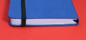 Caderno azul fechado em cima de superfície vermelha