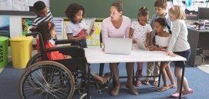 Professora em sala de aula, cercada de alunos, sendo que uma das estudantes está em uma cadeira de rodas