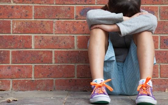 Criança de moletom e shorts cinza agachada com a cabeça entre as pernas