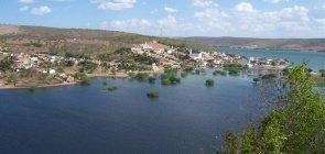 No centro da imagem, um largo rio com uma pequena cidade à sua margem e montanhas ao fundo.