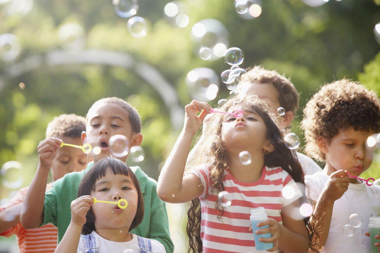 Grupo de crianças pequenas brincam com bolhas de sabão ao ar livre