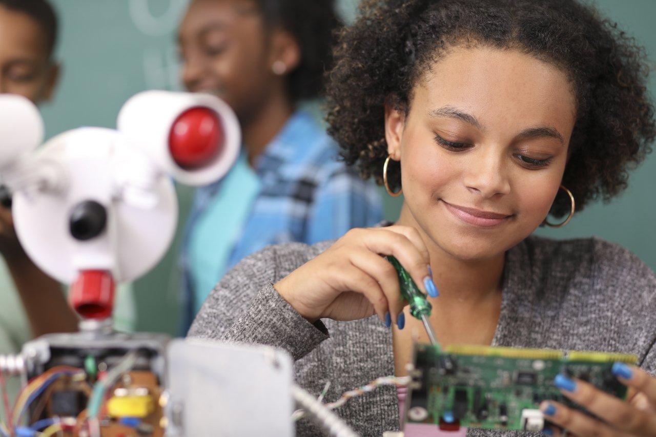 Uma menina com unhas pintadas de azul monta um robô em um laboratório de escola