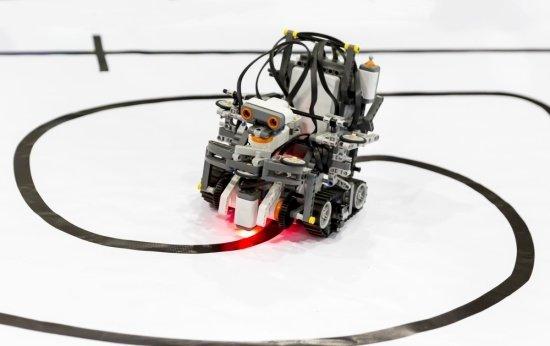 Robô programado por alunos se movimenta sobre uma superfície lisa