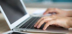 Imagem de um MacBook sendo utilizada por uma mulher. Só é possível ver as mãos da mulher