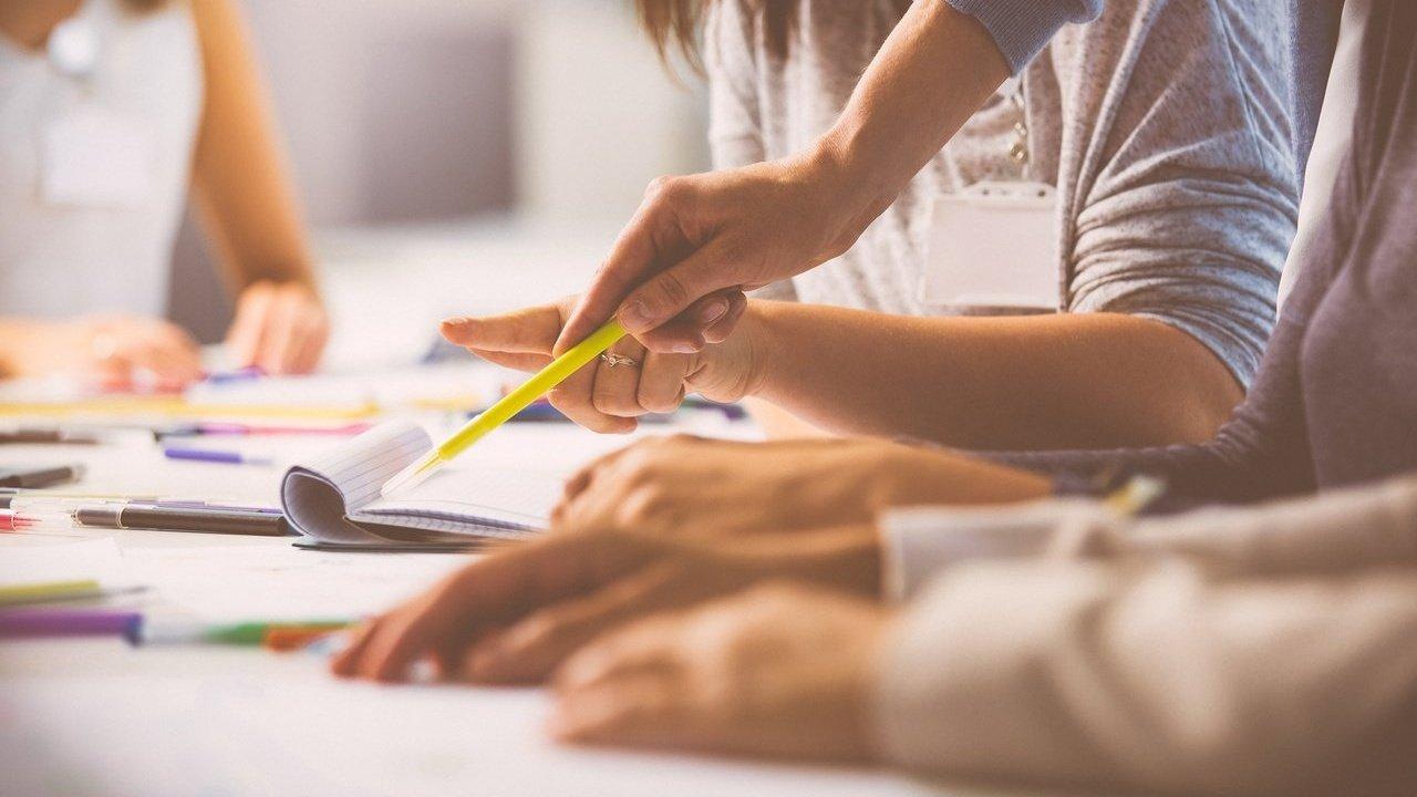 Pessoas reunidas em volta de uma mesa escrevem em cadernos