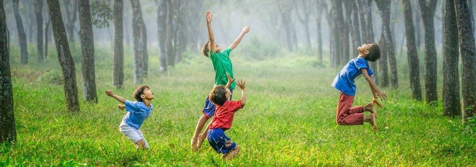 Quatro crianças brincando com uma bola que está no ar. Eles estão numa área verde cheia de árvores e mato