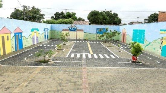 pátio restaurado com pintura nas paredes, circuitos desenhados no chão e canteiros de plantas