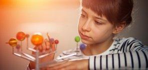 Menina constrói modelo do sistema solar com bolas e palitos para aula de Ciências
