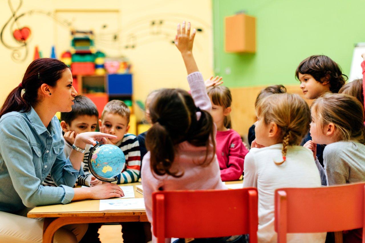 Professora sentada em uma mesa em sala de aula, com um globo terrestre à sua frente, cercada de crianças