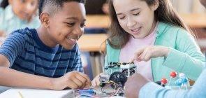 Duas crianças de cerca de 10 anos montando um protótipo de robótica