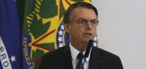 presidente Jair Bolsonaro em púlpito diante de bandeira do Brasil e da República