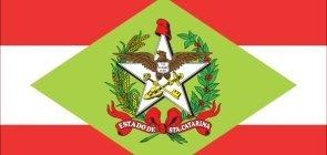 bandeira de santa catarina. duas faixas vermelhas horizontais divididas por uma faixa branca, com um losangulo verde do meio, uma estrela branca dentro dela e uma ave