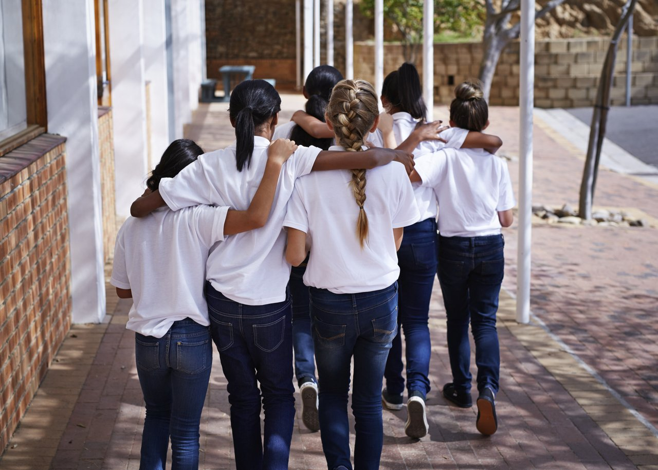 Adolescentes vestindo calças jeans e camisetas brancas caminham abraçadas perto de um muro de tijolos aparentes