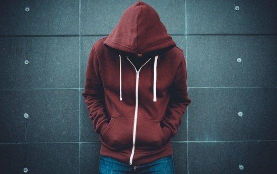 Foto de um adolescente com blusa de frio e gorro, de cabeça baixa e encostado na parede