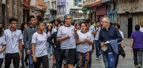 No centro de São Paulo, um grupo de alunos caminha com o professor. Destaca-se um dos alunos conversando com o professor