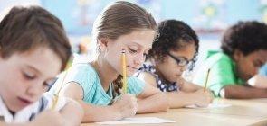 Crianças escrevem em sala de aula