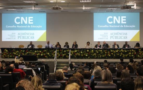 Mesa com os membros do Conselho Nacional de Educação e público da audiência em um auditório