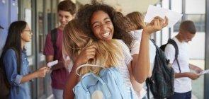 Duas adolescentes se abraçando no corredor da escola