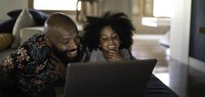 garota e homem (filha e pai) assistindo algo no notebook